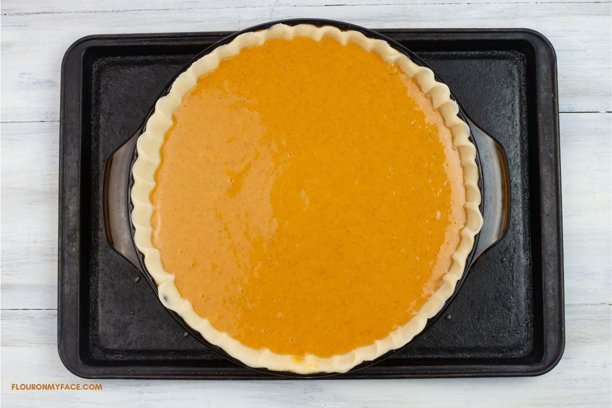 An unbaked pumpkin pie on a cookie sheet