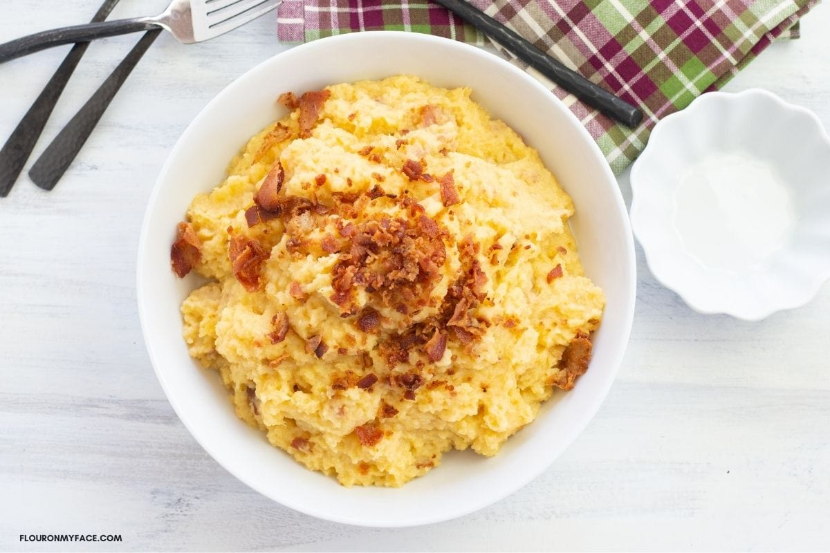 A serving bowl of Mashed Rutabaga topped with crumbled bacon.