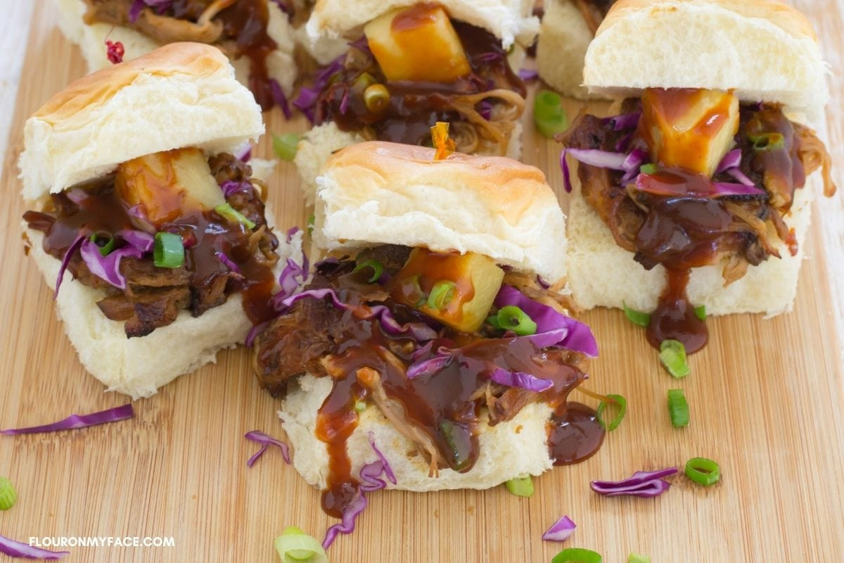 Pineapple pulled pork sliders on a cutting board.