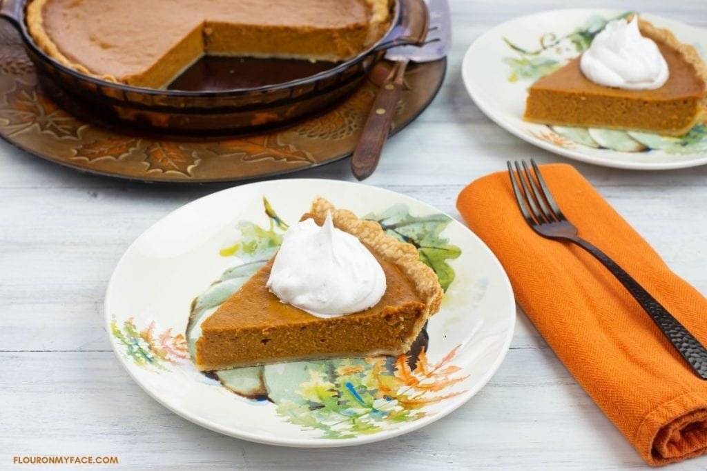 Sliced pumpkin pie topped with whipped cream on a plate.
