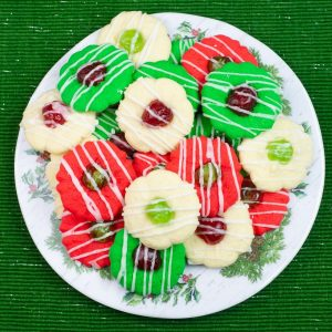 Red, green and white Christmas Spritz cookies on a holiday plate.