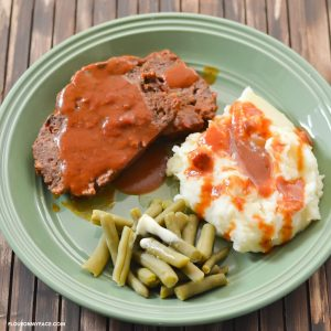 Sliced meatloaf, mashed potatoes, and green beans on a green dinner plate.