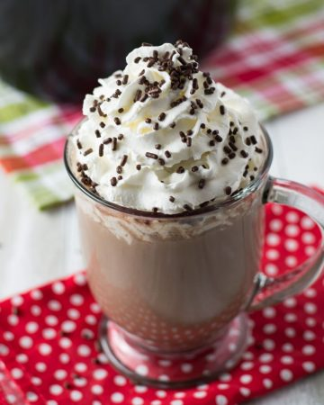 A mug of crock pot hot cocoa topped with whipped cream and sprinkles.