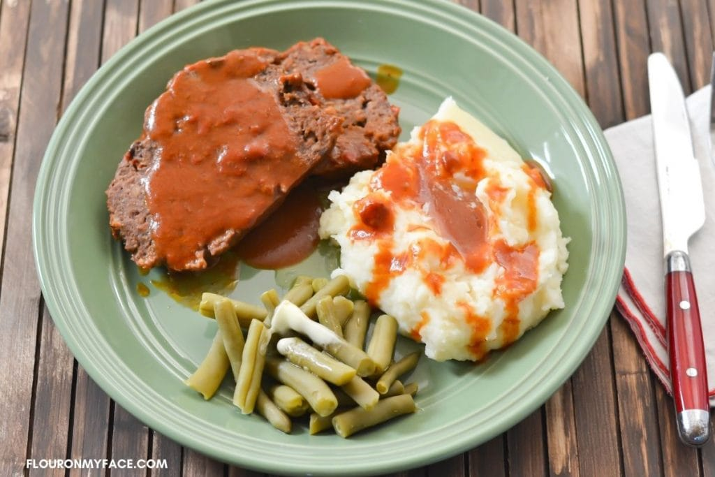 Dinner plate with meatloaf, mashed potatoes and green beans.