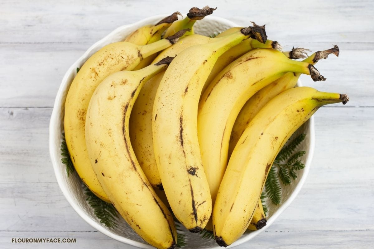 a bunch of fresh ripe bananas is a white bowl.