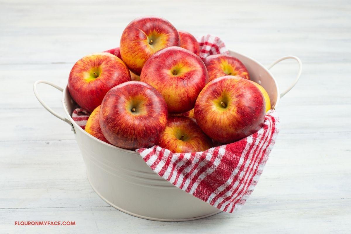 Honey Crisp apples in a white metal bucket.