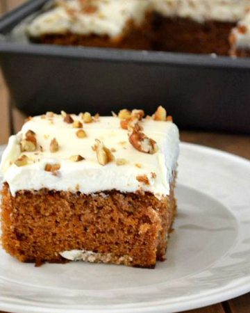 Closeup of a square piece of carrot cake with frosting.