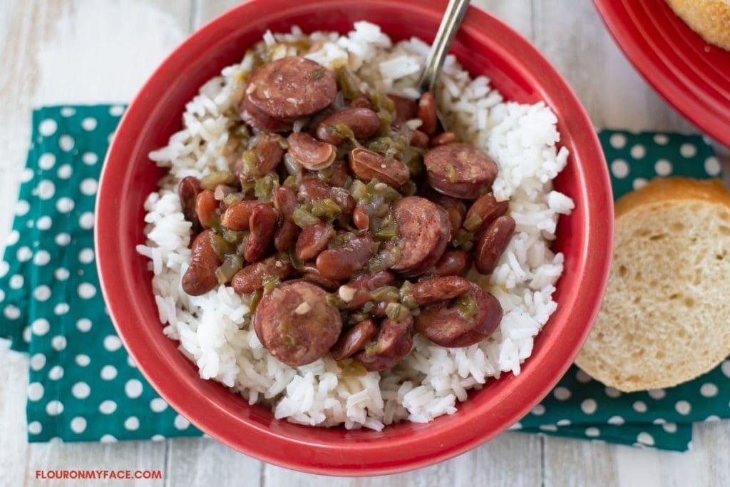 Red beans and rice over rice in a red bowl.