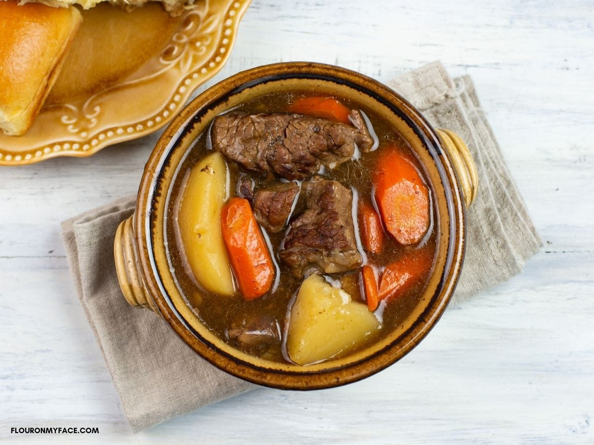 Classic beef stew in a brown bowl  on a napkin.