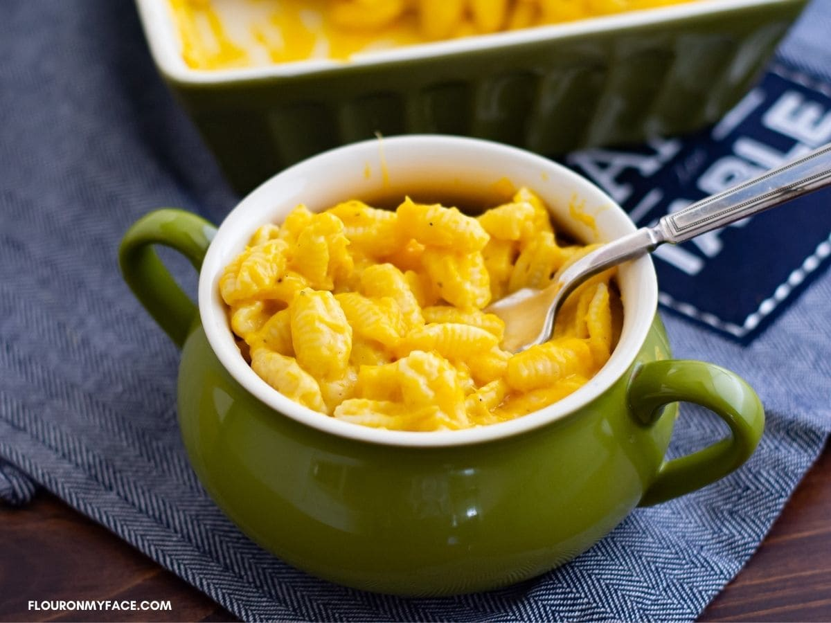 A green crock filled with squash mac and cheese.