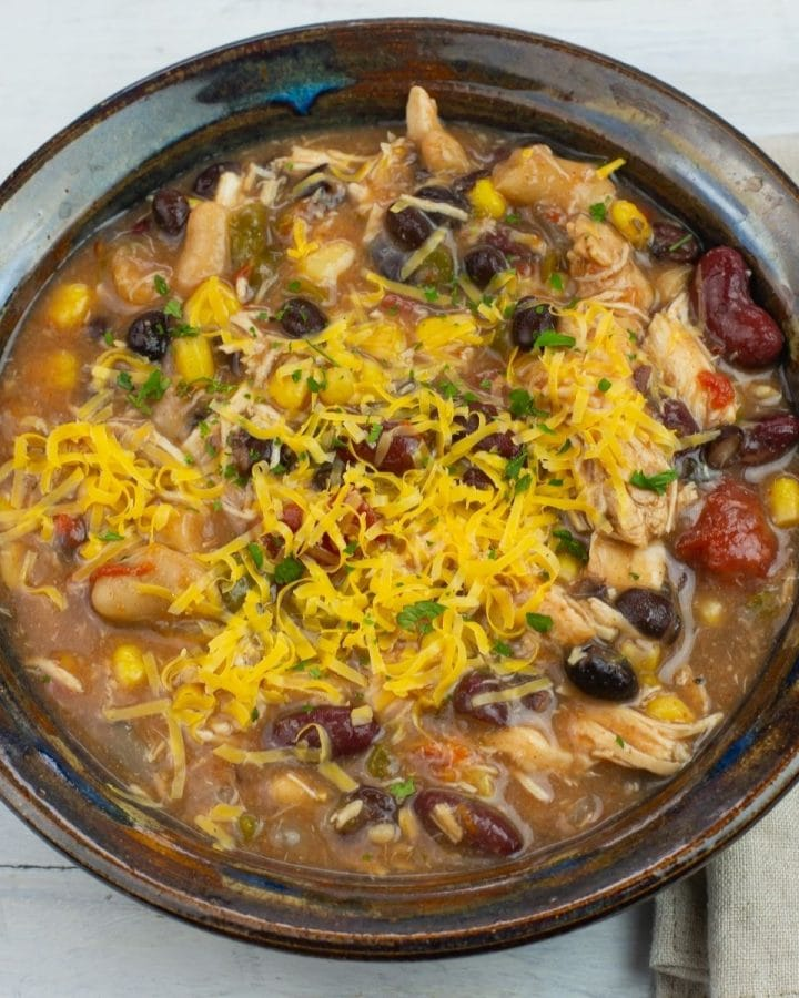 chicken chili topped with cheese in a bowl.