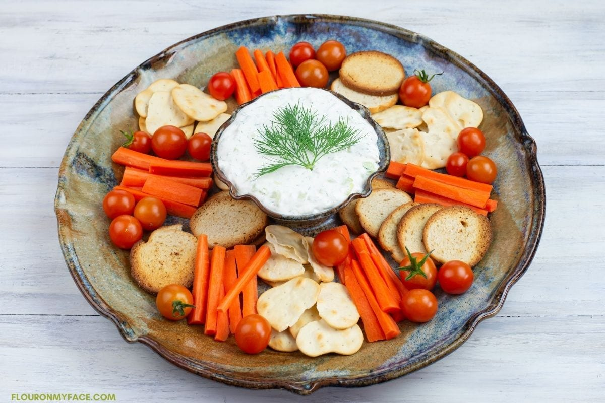 Cucumber Dill Dip served with vegetables and crackers in a dip serving platter.