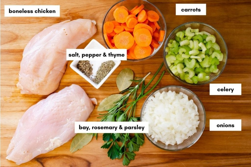 Chicken noodle soup ingredients on a wooden cutting board.
