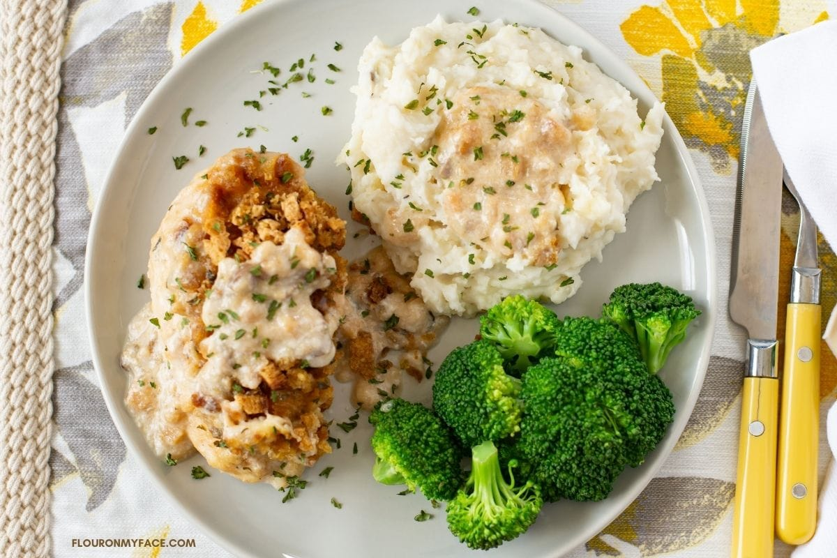 Swiss chicken with mashed potatoes and broccoli on a dinner plate.