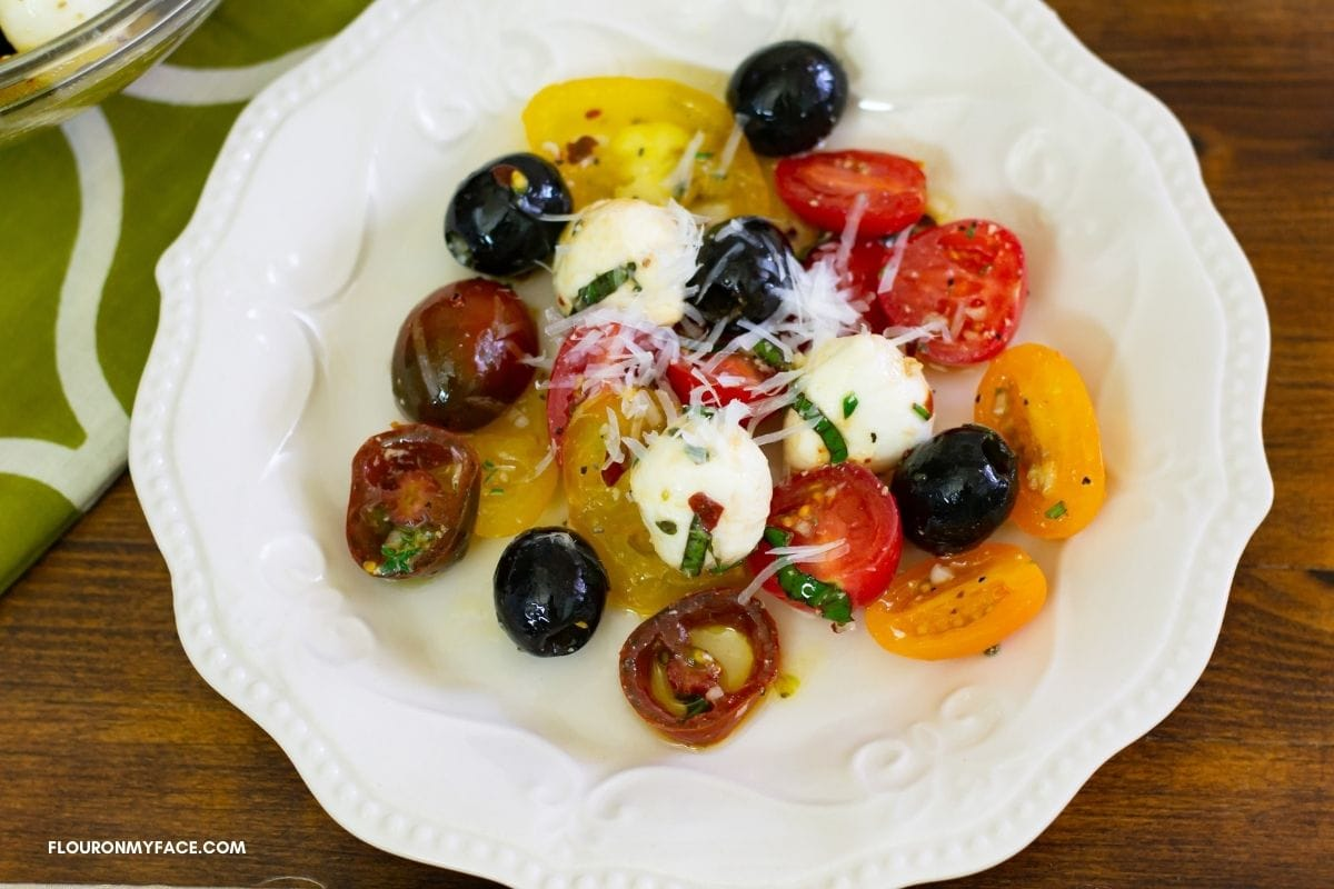 A salad of tomatoes, mozzarela and black olives on a salad plate.