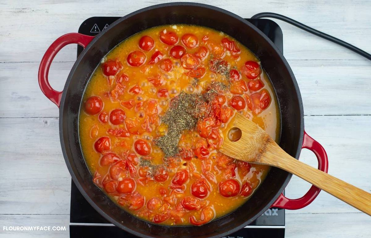 Adding herbs and spices to the burst tomatoes.