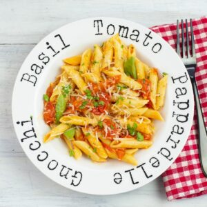 Pasta bowl filled with noodles tossed with cherry tomato sauce.