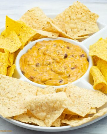 Chili Cheese Dip in a white serving dish with flour and corn chips.