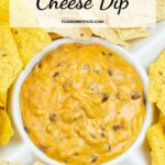 Long vertical image of a chip serving dish filled with chili cheese dip and chips.