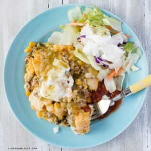 Overhead bowl filled with cornbread casserole with toppings.
