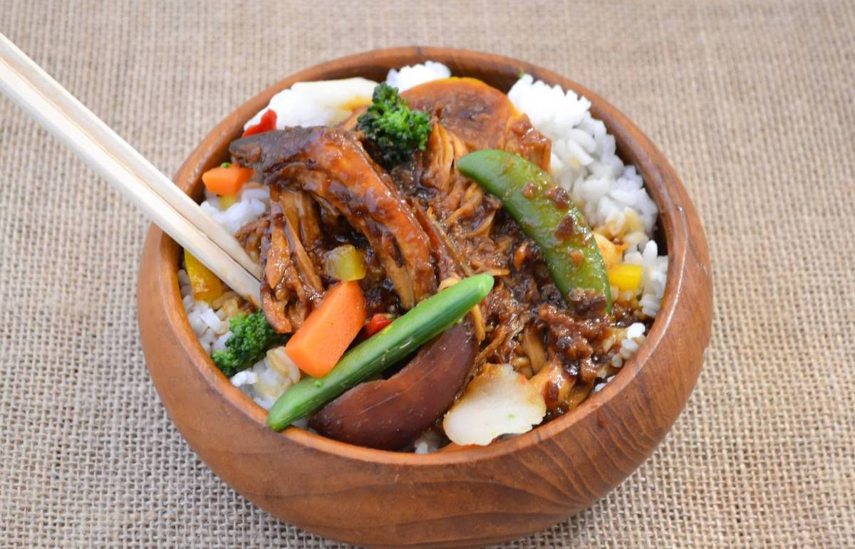 Brown wooden bowl filled with chicken teriyaki served over rice.