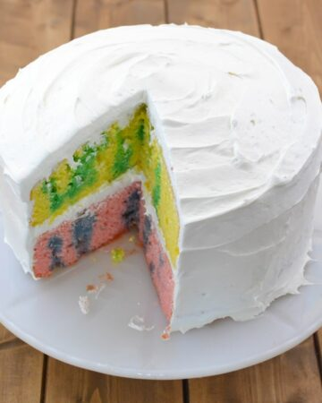 Easter Jello Poke Cake with a slice cut on a cake stand.