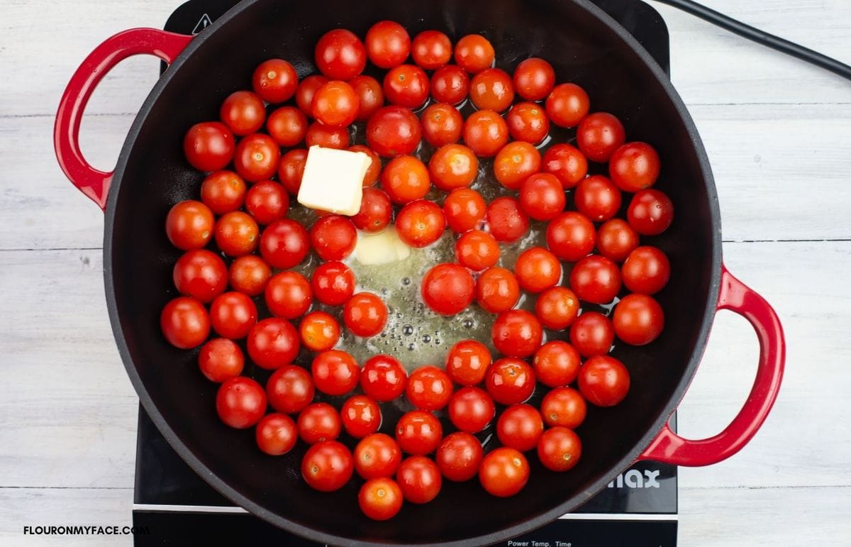 Overhead photo of cooking cherry tomatoes in olive oil and butter in a black skillet.