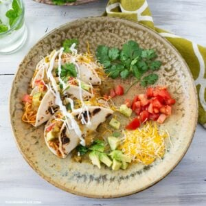 A plate with creamy chicken tacos covered in shredded cheese.