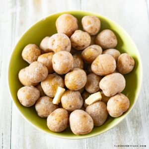 A bowl filled with Salt Potatoes with pats of butter.