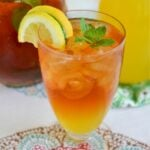 A tall glass filled with Mango Iced Tea with lemon slices and mint leaves garnish.