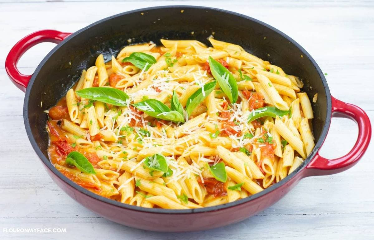Pasta, sauce, basil leaves and Parmesan cheese in a red skillet.