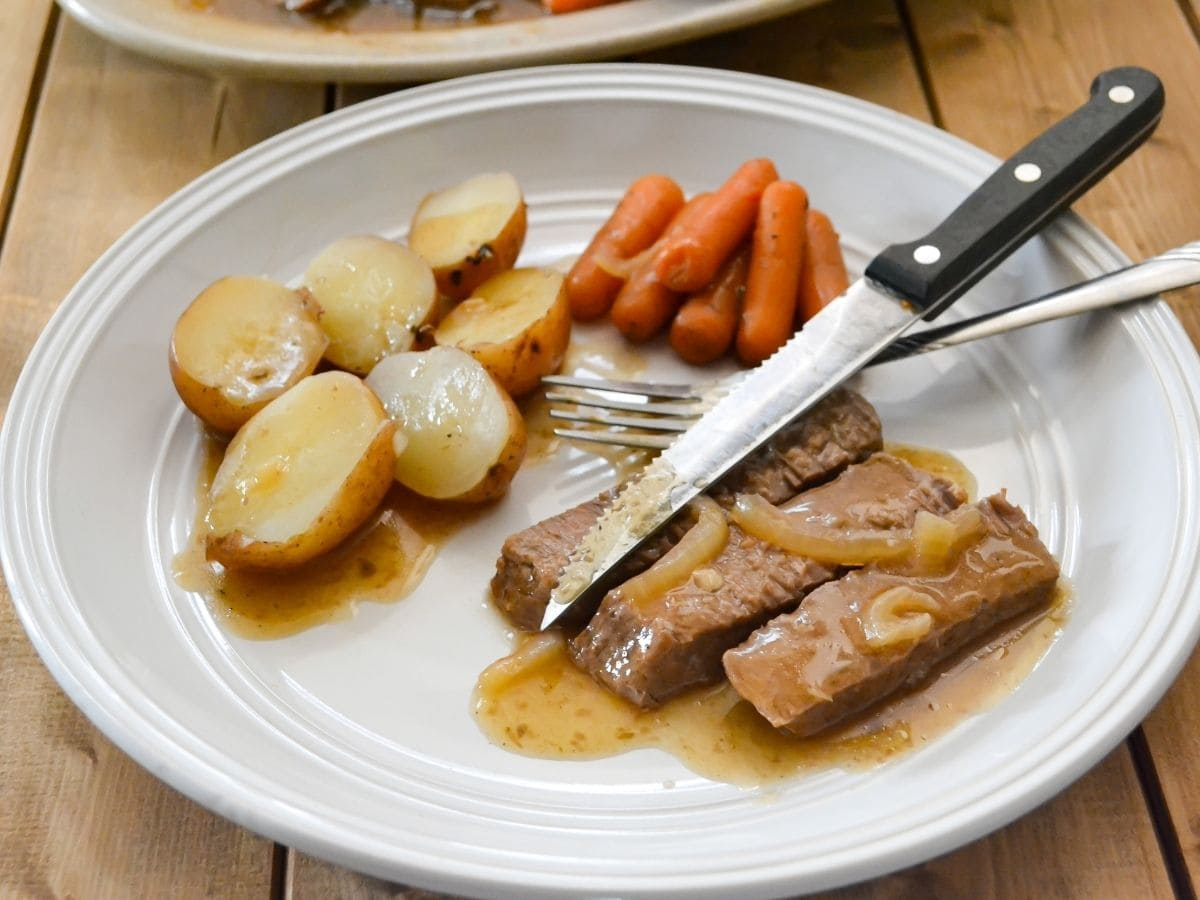 A dinner plate serving of London broil served with carrots and potatoes.