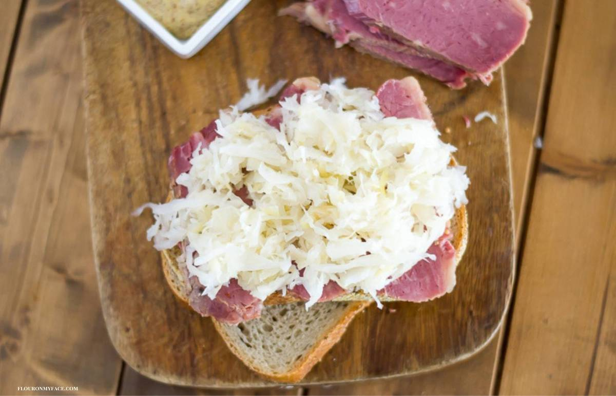 Making a corned beef sandwich on rye bread topped with sauerkraut.