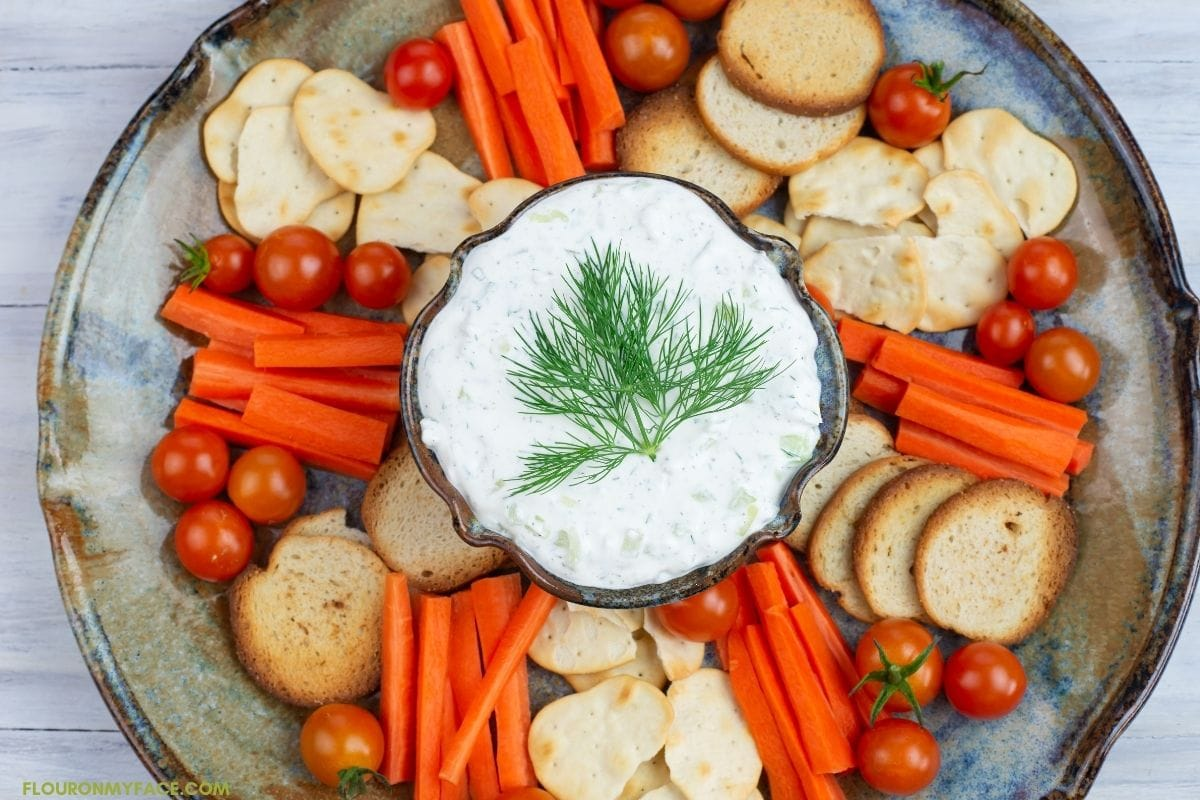 Dip served in a serving platter with carrots, cherry tomatoes and crackers.