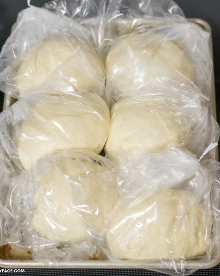 Bags of pizza dough on a sheet pan ready to go into the freezer.