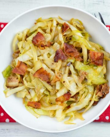 A white bowl filled with fried cabbage topped with crispy bacon pieces.