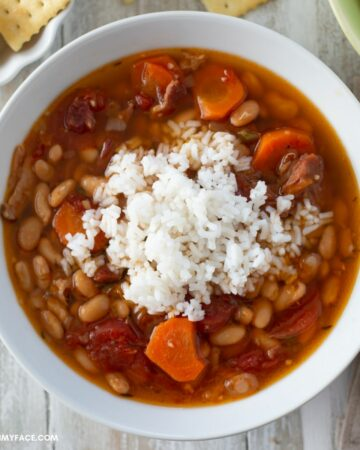 Ham and white bean soup topped with white rice in a serving bowl.