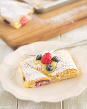 A lemon curd filled crescent bar topped with berries on a plate.