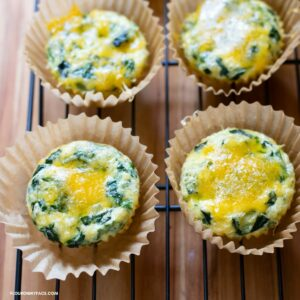 Breakfast muffins cooling on a wooden cutting board.