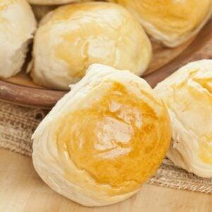 Buttery sweet dinner rolls in a basket on a wooden cutting board.