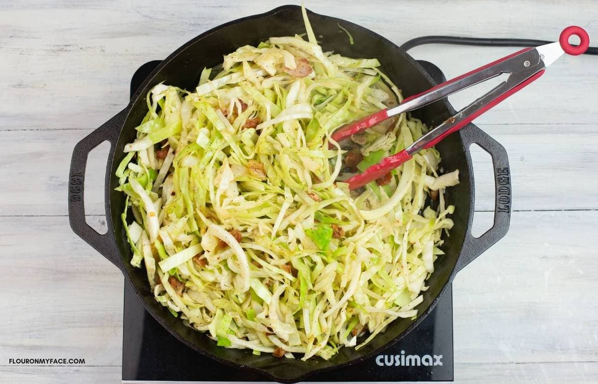 Tossing the cabbage with the seasonings in a skillet.