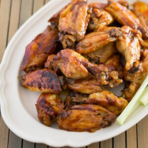 A serving platter with a stack of honey bbq buffalo chicken wings.