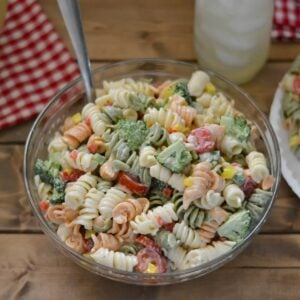 Glass bowl filled with broccoli and tomato pasta salad.