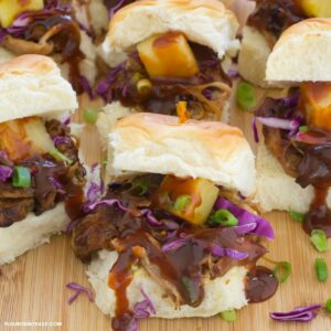 Pulled pork sliders topped with slaw on a cutting board.