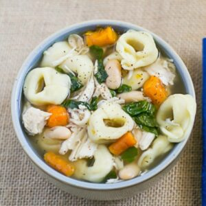 A soup bowl filled with chicken tortellini soup.