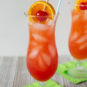 Classic Hurricane Cocktail served with ornage slice and cherry garnish in a hurricane glass.