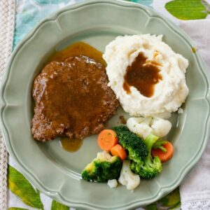 Crock Pot Cube Steak served with mashed potatoes and vegetables.