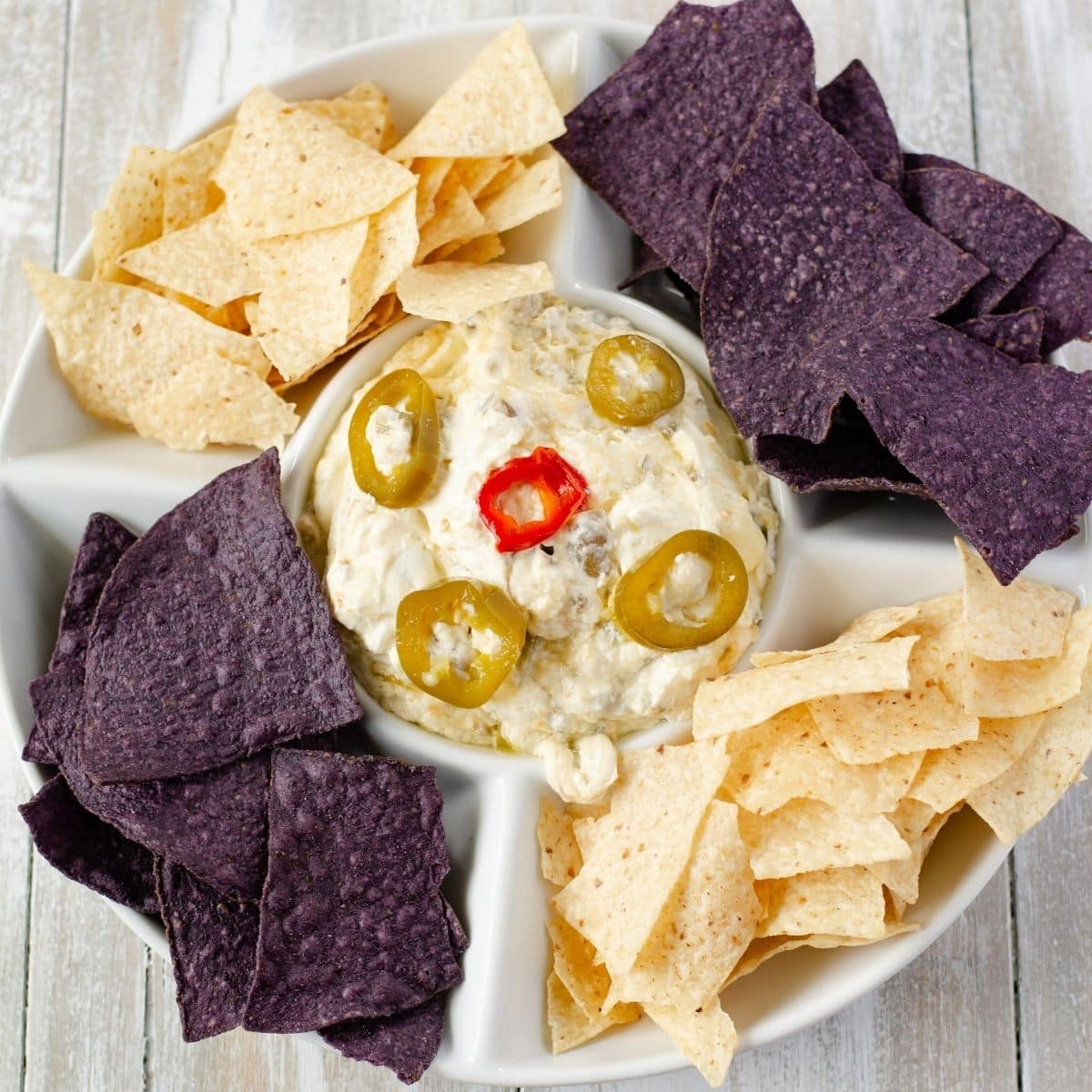 A dip bowl filled with jalapeno popper dip and chips.