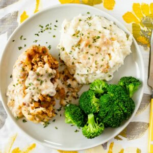Swiss chicken served with potatoes and broccoli on a dinner plate.