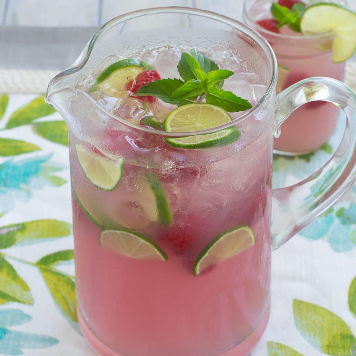 A glass pitcher full of pink lemonade.